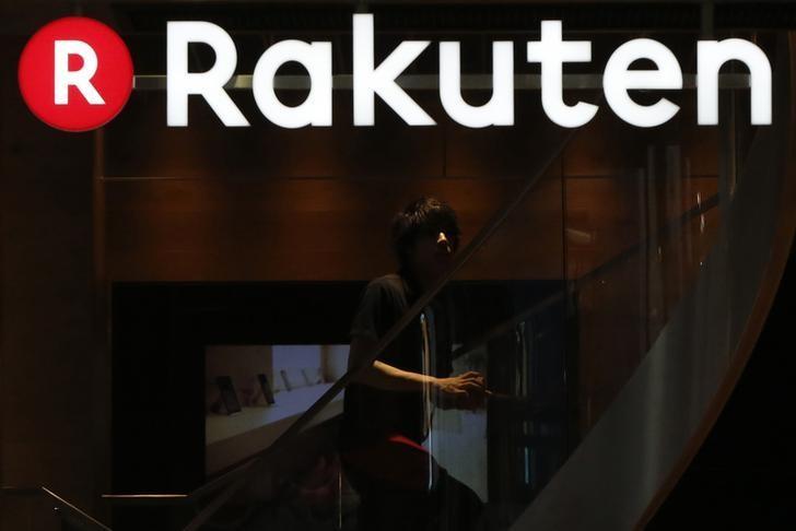 A staff of Rakuten Cafe is seen under a logo of Rakuten Inc at a shopping district in Tokyo August 4, 2014.  REUTERS/Yuya Shino