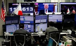 Валютные трейдеры за мониторами на фоне телеэкранов, транслирующих выступление президента США Дональда Трампа и динамику курса иены к доллару. Токио, 23 января 2017 года. Рынки акций в Европе и Азии снизились, а доллар ослаб к японской иене после того, как введенные Дональдом Трампом ограничения на въезд мигрантов усилили неопределенность в отношении экономических последствий политики нового президента США. REUTERS/Toru Hanai