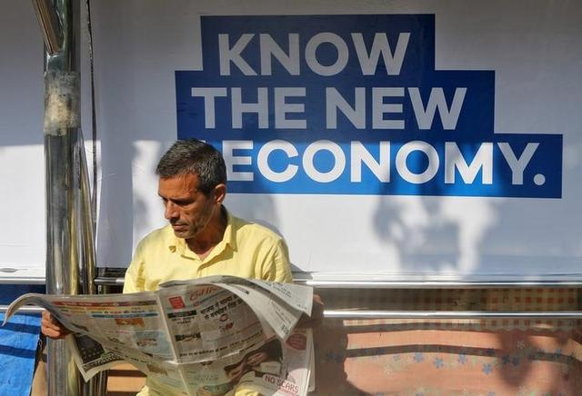 A man reads a newspaper as he waits for public transport at a bus stop in Mumbai,  January 31, 2017.  REUTERS/Shailesh Andrade