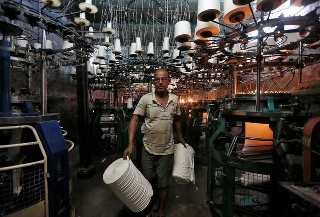 An employee carries cloth rolls inside an undergarment factory in Kolkata, India, February 1, 2017. REUTERS/Rupak De Chowdhuri/Files