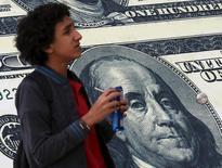 Мальчик проходит мимо обменного пункта с изображением американского доллара в Каире 21 февраля 2016 года. Доллар может лишь немного восстановиться в среду после худшего за три десятилетия начала года на фоне опасений о том, что США стремятся положить конец двадцатилетней политике сильного доллара. REUTERS/Mohamed Abd El Ghany