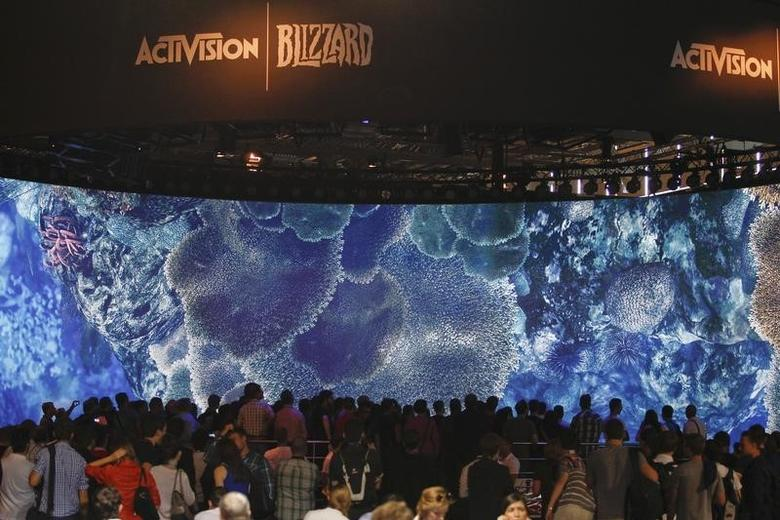 Visitors look at a presentation at the ActiVision Blizzard exhibition stand during the Gamescom 2013 fair in Cologne August 21, 2013.  REUTERS/Ina Fassbender