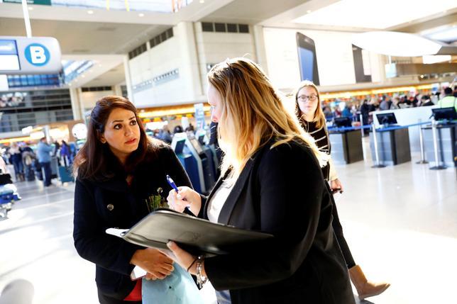 2月2日、米カリフォルニア州ロサンゼルスの連邦地裁は、イスラム圏の市民の入国を制限するトランプ大統領の大統領令について、対象7カ国の市民のうち移民ビザ保有者は入国を許可しなければならないとする仮判断を示した。写真はロサンゼルス国際空港でボランティアの移民弁護士に、親戚について相談しているイラン人女性(2017年 ロイター/Patrick T. Fallon)