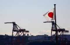 Japan's national flag is seen in front of containers and cranes at an industrial port in Tokyo, Japan, January 25, 2017.  REUTERS/Kim Kyung-Hoon
