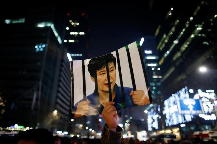 A man holds up a picture bearing an image of South Korean President Park Geun-hye as he attends a ceremony to celebrate the new year after a protest demanding Park's resignation, in Seoul, South Korea, December 31, 2016.   REUTERS/Kim Hong-Ji/Files
