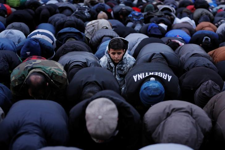 A boy looks up as demonstrators pray while participating in a protest by the Yemeni community against U.S. President Donald Trump's travel ban in the Brooklyn borough of New York, U.S., February 2, 2017.  REUTERS/Lucas Jackson