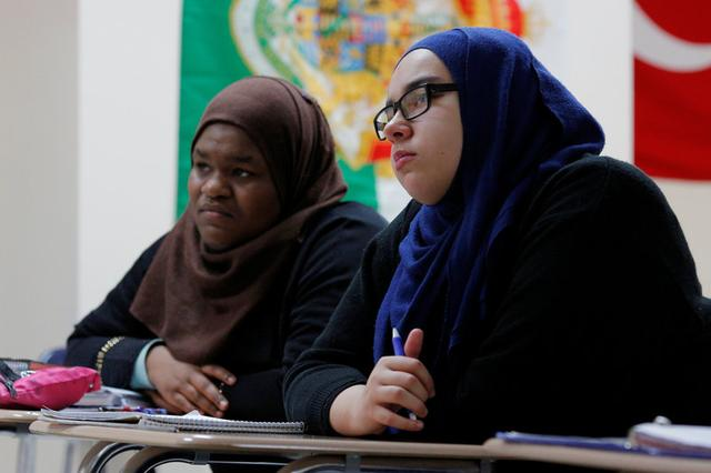 Tenth grade students Ayia Elsadig (L) and Sarah Sendian listen as Nadeem Mazen, Cambridge city councillor, Muslim and founder of JetPAC, speaks to their AP Government class at Al-Noor Islamic high school in Mansfield, Massachusetts, U.S. February 2, 2017. Picture taken February 2, 2017. REUTERS/Brian Snyder
