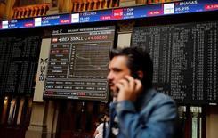 El Ibex-35 mantenía la tendencia alcista a media sesión el viernes, en una sesión marcada por el desplome de Banco Popular, que se anotaba un descenso cercano al 5 por ciento tras presentar unas pérdidas récord en 2016. En la imagen de archivo, un hombre habla por teléfono en la Bolsa de Madrid REUTERS/Andrea Comas