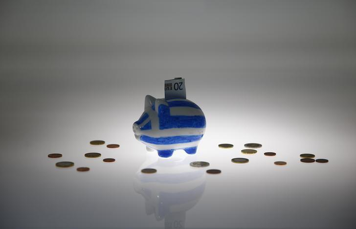 A piggybank painted in the colours of the Greek flag with a 20 euro banknote in it's slot, stands amongst various euro coins in this picture illustration taken in Berlin, Germany June 30, 2015. REUTERS/Pawel Kopczynski