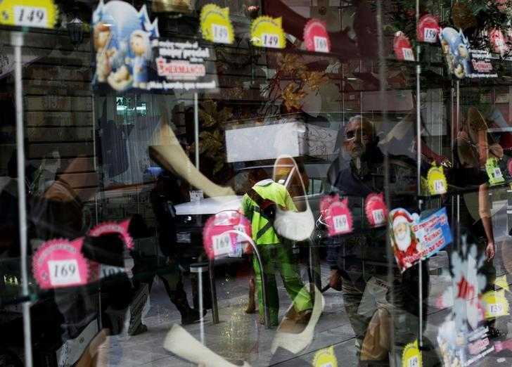 A man is reflected on a window at a shoe shop in downtown Mexico City November 21, 2014. REUTERS/Carlos Jasso/File Photo