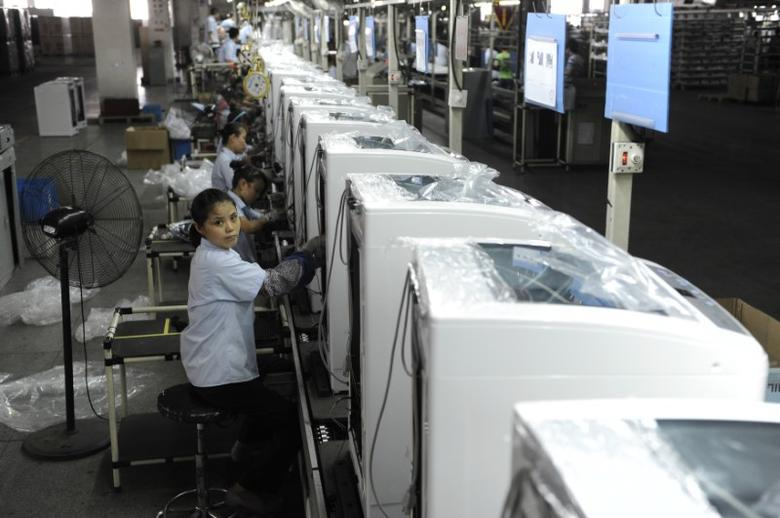 Employees assemble washing machines on the production line inside a factory of Hefei Rongshida Sanyo Electric in Hefei, Anhui province August 13, 2013.  REUTERS/Stringer/Files