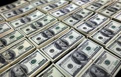 Долларовые купюры. Доллар начал неделю в обороне после выхода данных в США о заработной плате в январе, которая выросла менее ожидаемого, укрепив надежды, что ФРС воздержится от повышения ставок в следующем месяце. REUTERS/Guadalupe Pardo