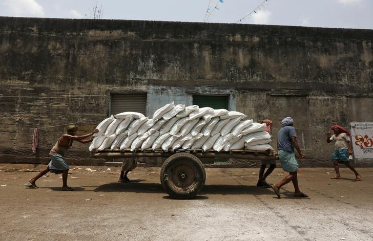Labourers push a handcart loaded with sacks of sugar at a wholesale market in Kolkata, India, April 26, 2016. REUTERS/Rupak De Chowdhuri/File Photo