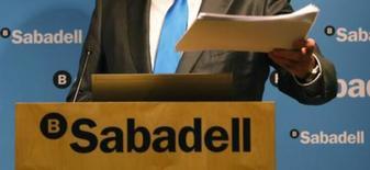 El banco Sabadell dijo el martes que espera cerrar 2017 con un beneficio neto de 800 millones de euros, lo que representaría un incremento del 13 por ciento frente a 2016 gracias al crecimiento de las comisiones y una estabilización de sus márgenes financieros. En la imagen de archivo, el presidente de Sabadell,  Josep Oliu, muestra un dosier sobre los resultados del grupo durante una conferencia de prensa en su sede en Barcelona REUTERS/Gustau Nacarino