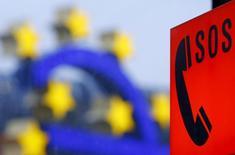 Телефон для связи с экстренными службами на фоне символа валюты евро у здания ЕЦБ во Франкфурте-на-Майне 19 января 2016 года. Европейский центробанк в понедельник отверг обвинения США в валютных манипуляциях и предупредил, что дерегулирование банковского сектора, которое сейчас открыто обсуждается в Вашингтоне, может создать предпосылки для нового финансового кризиса. REUTERS/Kai Pfaffenbach
