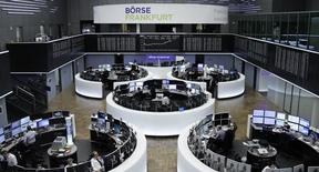 Traders work at their desks in front of the German share price index, DAX board, at the stock exchange in Frankfurt, Germany, February 1, 2017. REUTERS/Staff/Remote