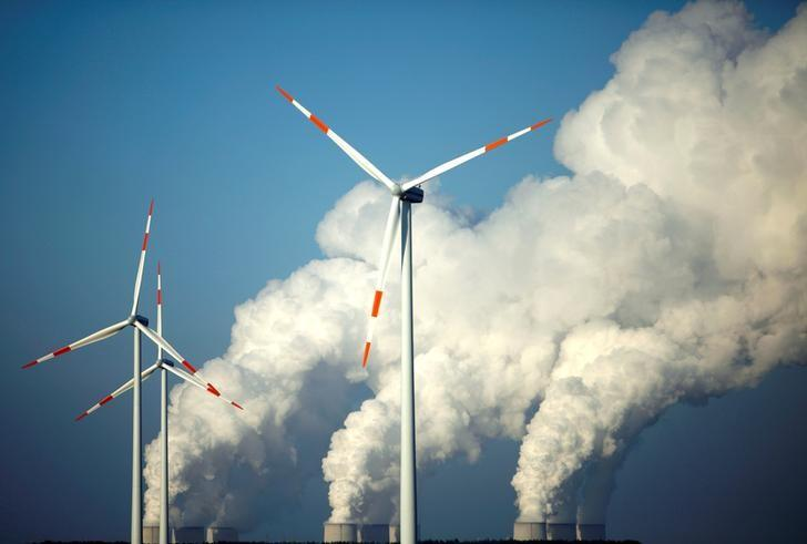 Steam billows from the cooling towers of Vattenfall's Jaenschwalde brown coal power station behind wind turbines near Cottbus, Germany, December 2, 2009.    REUTERS/Pawel Kopczynski/File Photo
