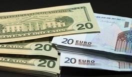 Доллары и евро. Доллару удалось стабилизироваться на торгах четверга после падения в предыдущую сессию, хотя сохраняющееся неприятие риска подтолкнуло доходность казначейских облигаций к многонедельным минимумам и ограничило восстановление американской валюты.  REUTERS/Philippe Wojazer  (FRANCE - Tags: BUSINESS)