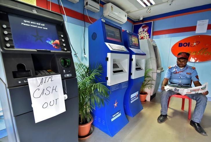 A security guard reads a newspaper inside an ATM counter as a notice is displayed on an ATM in Guwahati, India, November 27, 2016. REUTERS/Anuwar Hazarika/Files