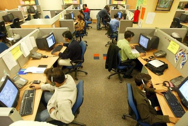 Indian engineers attend to calls from abroad inside a call centre in Gurgaon December 3, 2003. REUTERS/Kamal Kishore/Files