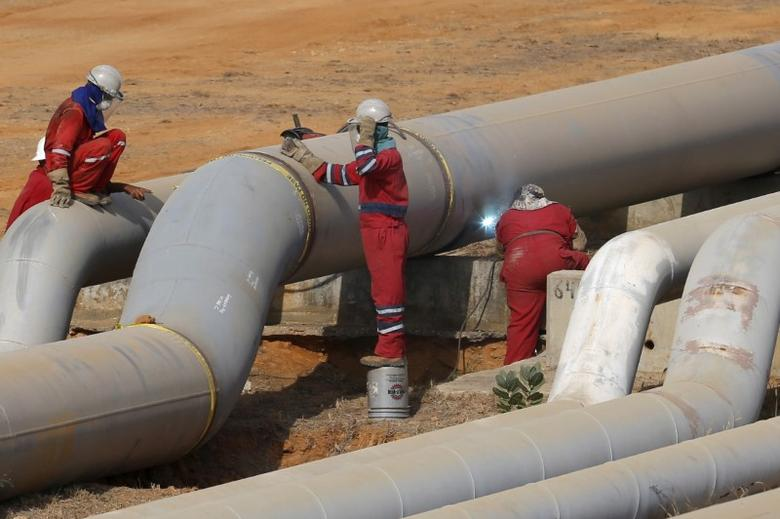 FILE PHOTO: Oil workers weld a pipeline at PDVSA's Jose Antonio Anzoategui industrial complex in the state of Anzoategui, Venezuela, April 15, 2015. REUTERS/Carlos Garcia Rawlins/File Photo
