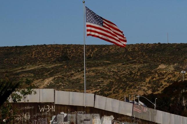 2月9日、米国がメキシコ国境沿いに建設する壁について、国土安全保障省の内部報告書で最大216億ドルの費用と3年以上の期間が必要との見積もりが示されたことが明らかになった。ロイターが同報告書を確認した。写真は米・メキシコ国境の壁ではためく米国旗。メキシコ・ティフアナ側から撮影(2017年 ロイター/Jorge Duenes)