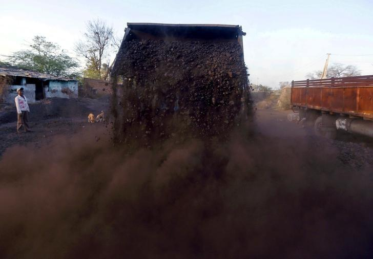 A worker watches as a loader unloads coal at a yard on the outskirts of Ahmedabad, India, February 12, 2016.  REUTERS/Amit Dave/File Photo