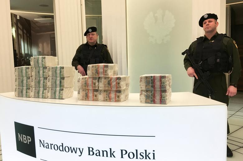 Security men at the Polish central bank headquarters guard piles of cash worth 1 million zlotys each (199,110 pounds) in 100-zloty, 200-zloty and 500-zloty banknotes in Warsaw, Poland February 10, 2017.  REUTERS/Marcin Goettig
