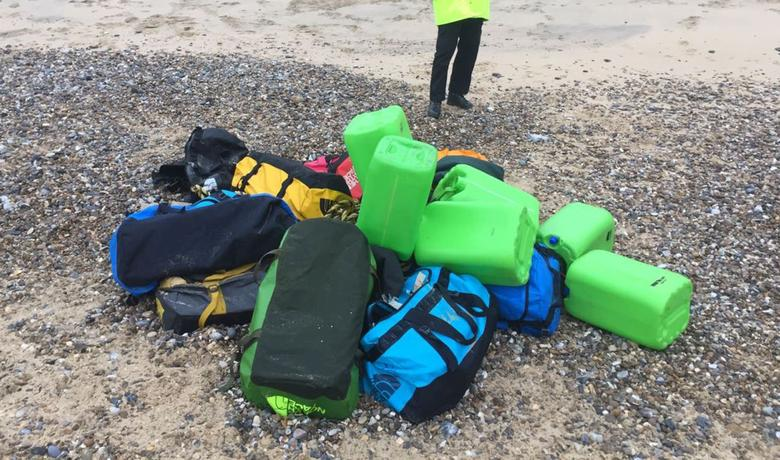 A law enforcement officer stands by holdalls containing cocaine that were washed up on Hopton Beach, near Great Yarmouth, Britain February 9, 2017.  National Crime Agency/Handout via Reuters