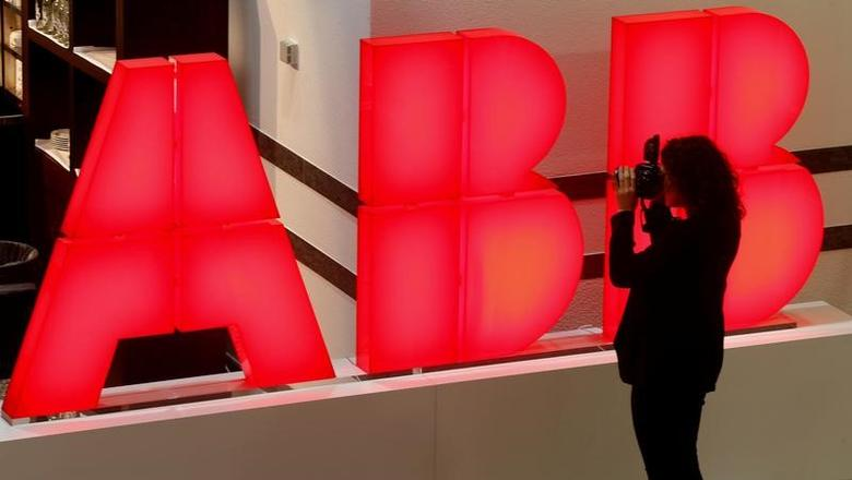 A woman takes pictures of the logo of Swiss power technology and automation group ABB ahead of a news conference to present the company's full-year results in Zurich, Switzerland February 8, 2017.  REUTERS/Arnd Wiegmann