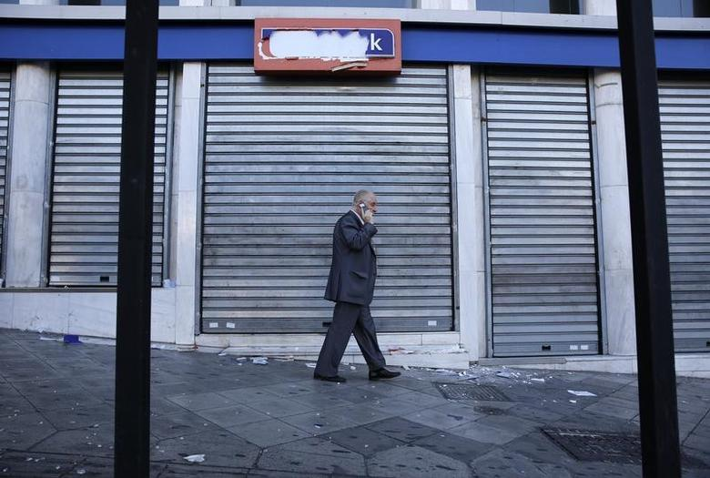 A pedestrian walks by a damaged branch of Eurobank after brief clashes between police and protesters during a 24-hour general strike in central Athens, Greece, November 12, 2015.  REUTERS/Yannis Behrakis