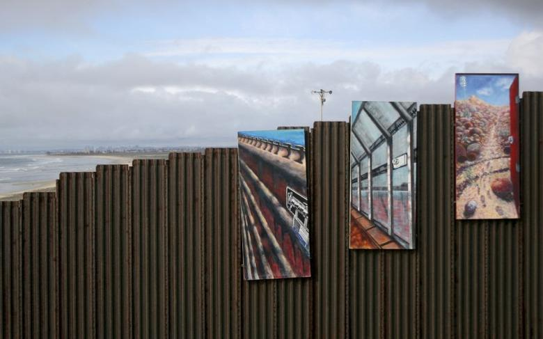 A section of the Mexico-U.S. border wall is seen decorated with paintings February 20, 2008. REUTERS/Jorge Duenes