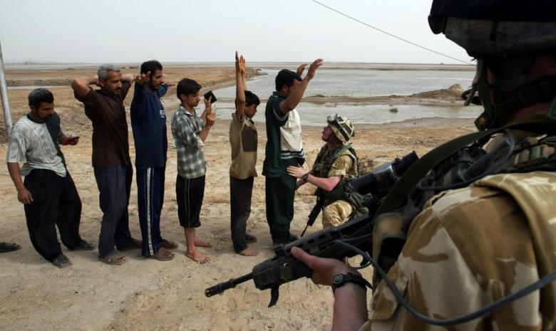 File Photo: Iraqi men are frisked by a British Army soldier before being allowed to re-enter the southern city of Basra March 31, 2003. REUTERS/Chris Helgren/File Photo
