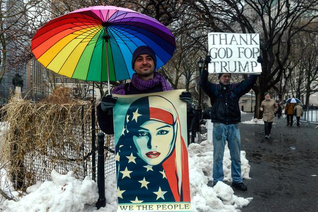 A man participating in a protest against U.S. President Donald Trump's immigration policy at the Jewish Rally for Refugees stands in front of a Trump supporter in New York City, U.S. February 12, 2017. REUTERS/Stephanie Keith