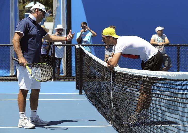 Spain's Rafael Nadal leans on the net as he talks to his coach Toni Nadal during a practice session at Melbourne Park, Australia, January 17, 2016. REUTERS/Jason O'Brien/Files