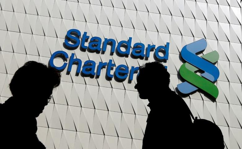 Passersby walk in front of the main branch of Standard Chartered in Hong Kong, January 8, 2015. REUTERS/Bobby Yip/File Photo