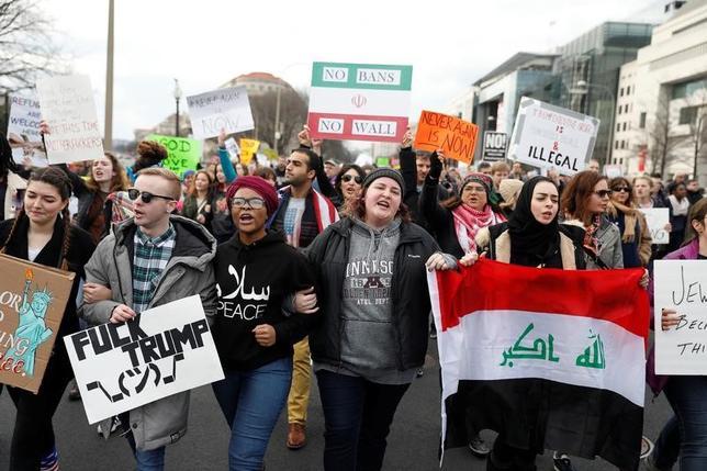 2月14日、イスラム圏7カ国からの入国を制限する大統領令の一時差し止めを命じたワシントン州シアトル連邦地裁の決定をめぐり、司法省は控訴裁での審理が完全に終了するまで法廷の手続きを停止するよう要請したが、同地裁の判事は13日、これを却下した。写真はトランプ大統領の移民政策に反対する人々。ワシントンで1月撮影(2017年 ロイター/Aaron P. Bernstein TEMPLATE OUT)