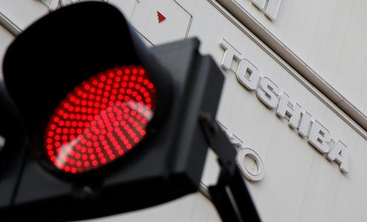A logo of Toshiba Corp is seen behind a red light signal outside an electronics retail store in Tokyo, Japan, January 19, 2017. REUTERS/Toru Hanai/Files