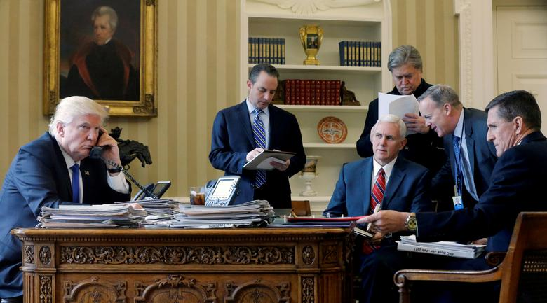 FILE PHOTO: U.S. President Donald Trump (L-R), joined by Chief of Staff Reince Priebus, Vice President Mike Pence, senior advisor Steve Bannon, Communications Director Sean Spicer and National Security Advisor Michael Flynn, speaks by phone with Russia's President Vladimir Putin in the Oval Office at the White House in Washington, U.S. January 28, 2017. REUTERS/Jonathan Ernst