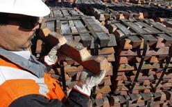 Un trabajador revisa un cargamento de cobre en la refinería Ventanas de la estatal Codelco en Ventanas, Chile, abr 16, 2012. El cobre cerró en baja el martes por esperanzas en que las negociaciones por una huelga se reinicien en la mayor mina mundial del metal en Chile, mientras que el aluminio tocó su nivel más alto en 21 meses por preocupaciones por el posible cierre de fundiciones en China para reducir la contaminación.  REUTERS/Eliseo Fernandez