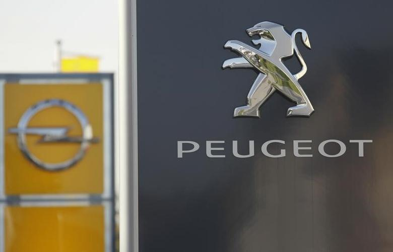 The logos of German General Motors daughter Opel and French car maker Peugeot are seen at a Opel and Peugeot dealership in Leverkusen near Cologne October 22, 2012.  Picture taken October 22.  REUTERS/Wolfgang Rattay