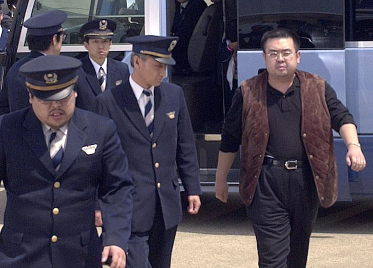 A man (R) believed to be North Korean heir-apparent Kim Jong Nam, is escorted by police as he boards a plane upon his deportation from Japan at Tokyo's Narita international airport in Narita, Japan, in this photo taken by Kyodo May 4, 2001. Mandatory credit Kyodo/via REUTERS/Files