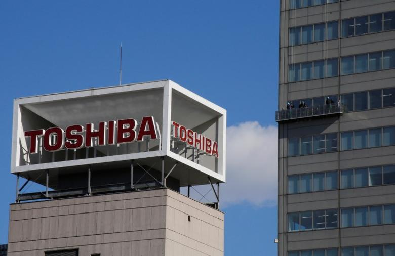 The logo of Toshiba Corp is seen as Window cleaners work on the company's headquarters in Tokyo, Japan, February 14, 2017. REUTERS/Toru Hanai