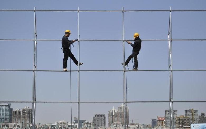 Workers stand on a steel frame which they are welding for an advertising board in Jiaxing, Zhejiang province March 24, 2012. China should be ready to cope with ''extreme risks'' in the economy from a sharper global downturn, although the country is on track to grow a healthy 8.5 percent this year, a senior economist at the cabinet's think-tank said on Thursday. REUTERS/Stringer (CHINA - Tags: BUSINESS CONSTRUCTION) CHINA OUT. NO COMMERCIAL OR EDITORIAL SALES IN CHINA - RTR2ZSON
