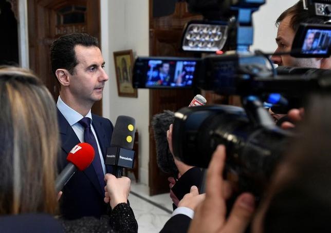 2月16日、シリアのアサド大統領(写真左)は、シリアから米国への入国を禁止したトランプ米大統領の政策は「シリア国民が対象ではない」と、同日に放送されたフランスの番組で語った。国営通信SANAから1月に提供されたもの(2017年 ロイター/SANA/Handout via Reuters)
