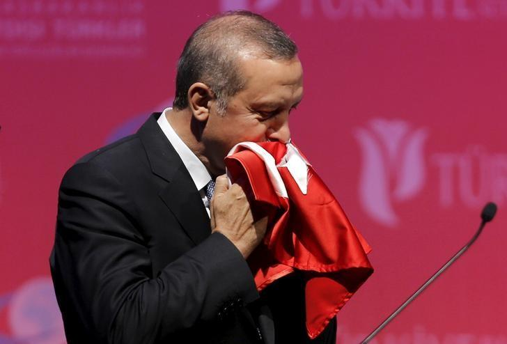 Turkey's President Tayyip Erdogan kisses a handmade Turkish flag, given to him as a gift from Ugandan university student Cemil (not pictured), during a graduation ceremony in Ankara, Turkey, June 11, 2015. REUTERS/Umit Bektas/File Photo