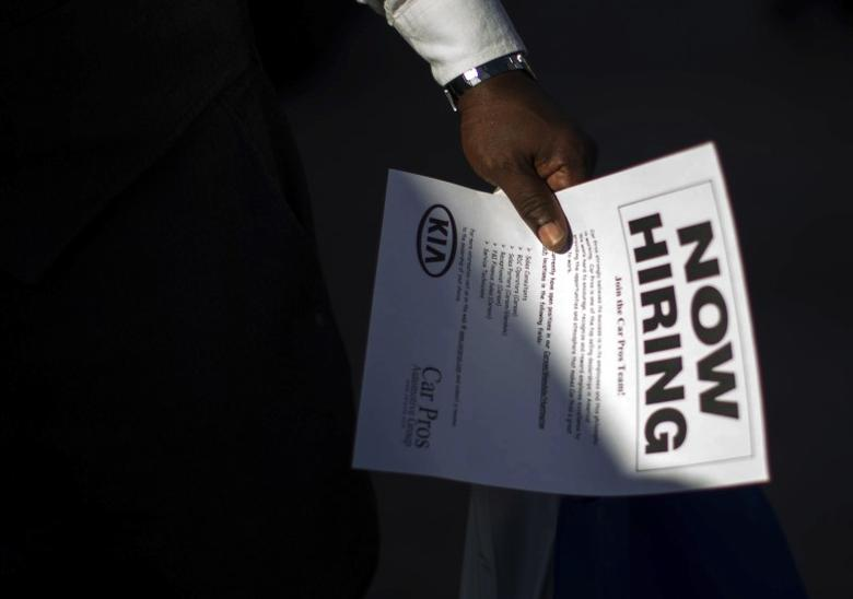 A man holds a leaflet at a military veterans' job fair in Carson, California October 3, 2014.  REUTERS/Lucy Nicholson