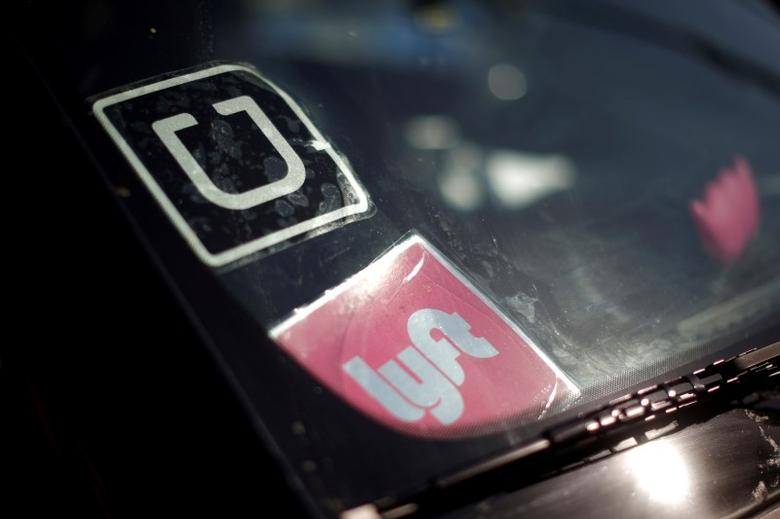 A driver displays Uber and Lyft ride sharing signs in his car windscreen in Santa Monica, California, U.S., May 23, 2016.  About a half dozen ride-hailing firms have rushed into Texas tech hub Austin after market leaders Uber and Lyft left the city a little over a monthago in a huff over municipal requirements that they fingerprint drivers.    REUTERS/Lucy Nicholson/