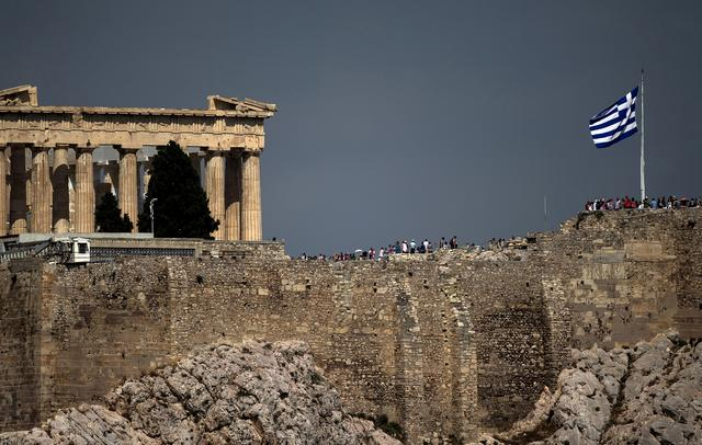 FILE PHOTO:A Greek flag flutters in front of the ancient Parthenon temple atop the Acropolis hill archaeological site in Athens, Greece, June 26, 2015.   REUTERS/Marko Djurica/File Photo