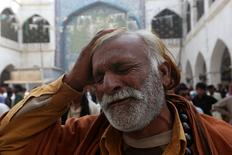 A man beats his head as he mourns the death of a relative who was killed in a suicide blast at the tomb of Sufi saint Syed Usman Marwandi, also known as the Lal Shahbaz Qalandar shrine, on Thursday evening in Sehwan Sharif, Pakistan's southern Sindh province, February 17, 2017. REUTERS/Akhtar Soomro